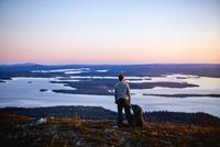 Hiker enjoying sunset at lake, Keimiotunturi, Lapland, Finland