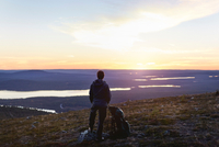 Hiker enjoying sunset at lake, Keimiotunturi, Lapland, Finland