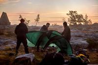 Hikers setting up tent at sunset, Sarkitunturi, Lapland, Finland