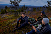 Hikers relaxing with coffee on hilltop, Keimiotunturi, Lapland, Finland