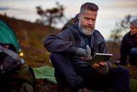 Hiker using digital tablet by tent, Keimiotunturi, Lapland, Finland