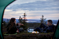 Hikers relaxing, chatting in front of tent, Keimiotunturi, Lapland, Finland