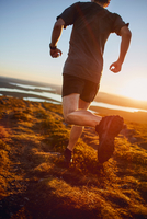 Man running on cliff top at sunset, Keimiotunturi, Lapland, Finland 11015297236| 写真素材・ストックフォト・画像・イラスト素材|アマナイメージズ