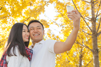 Young couple taking smartphone selfie in autumnal park, Beijing, China