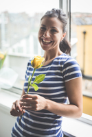 Portrait of happy young woman in apartment holding yellow rose 11015297462| 写真素材・ストックフォト・画像・イラスト素材|アマナイメージズ