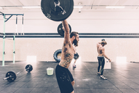 Young male cross trainer snatch lifting barbell in gym