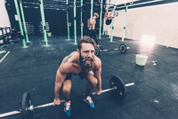 Young male cross trainer preparing to lift barbell in gym