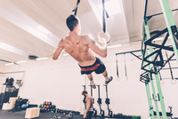 Rear view of male cross trainer training on gymnastic rings