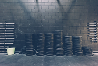 Stacked rows of barbell weights in black gym