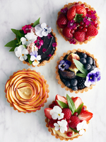 Display of variety of tart, fruit and flowers