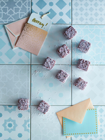 Cubes of sweets on tiles, next to greeting cards