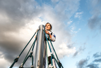 Boy in astronaut costume gazing at top of climbing frame against dramatic sky
