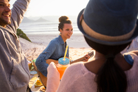 Young adult friends playing guitar and picnicing at beach, Cape Town, Western Cape, South Africa