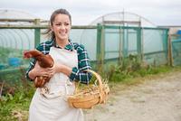 Woman on chicken farm holding chicken