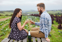 Couple in rural location sitting on pallets making a toast