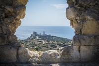 View of lighthouse through hole in stone wall, Cagliari, Masua, Sardinia, Italy