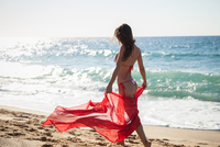 Woman on beach wearing bikini carrying sarong, Piscinas, Sardinia, Italy