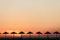 Silhouette of parasols at sunset, Piscinas, Sardinia, Italy