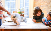 Child and mother playing with papier mache