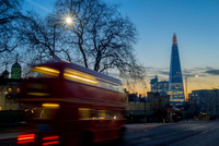 Blurred motion of bus passing The Shard and Tower of London, London, UK