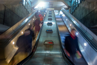 Blurred motion of people on escalator, London, UK