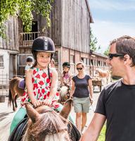 Father guiding daughter riding horse 11015298199| 写真素材・ストックフォト・画像・イラスト素材|アマナイメージズ