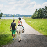 Rear view of father guiding daughter riding horse, Fuessen, Bavaria, Germany