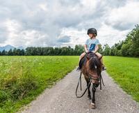 Boy horse riding, Fuessen, Bavaria, Germany 11015298205| 写真素材・ストックフォト・画像・イラスト素材|アマナイメージズ
