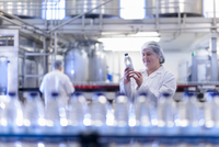 Female worker inspecting water bottle on production line in spring water factory 11015298292| 写真素材・ストックフォト・画像・イラスト素材|アマナイメージズ