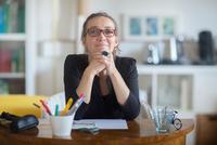 Portrait of mature woman sitting at desk 11015298327| 写真素材・ストックフォト・画像・イラスト素材|アマナイメージズ