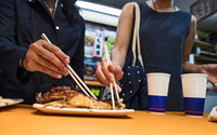 Two friends eating fish at the Nishiki street market in Kyoto, Japan