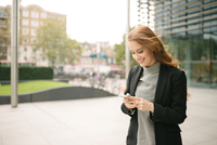 Woman in city looking at smartphone smiling
