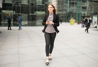 Woman walking in city holding smartphone