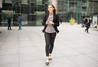 Woman walking in city holding smartphone 11015298342| 写真素材・ストックフォト・画像・イラスト素材|アマナイメージズ