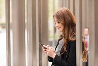 Businesswoman in city looking at smartphone 11015298354| 写真素材・ストックフォト・画像・イラスト素材|アマナイメージズ