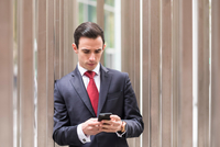 Businessman in city looking at smartphone