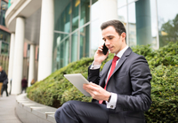 Businessman in city making telephone call, using digital tablet