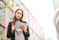 Businesswoman in city using digital tablet 11015298361| 写真素材・ストックフォト・画像・イラスト素材|アマナイメージズ