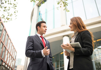 Businesspeople in city chatting 11015298363| 写真素材・ストックフォト・画像・イラスト素材|アマナイメージズ