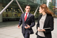 Businesspeople in city walking and talking