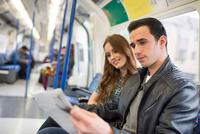 Couple on train reading newspaper