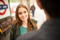 Woman on railway platform looking at friend smiling 11015298381| 写真素材・ストックフォト・画像・イラスト素材|アマナイメージズ