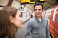 Man on railway platform talking to friend