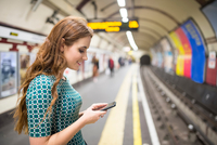 Side view of woman on railway platform looking at smartphone