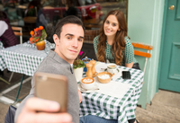 Couple at pavement cafe talking selfie