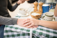 Cropped view of couple holding hands at cafe table 11015298402| 写真素材・ストックフォト・画像・イラスト素材|アマナイメージズ