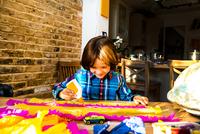 Boy spreading glue on crepe paper to make pinata 11015298482| 写真素材・ストックフォト・画像・イラスト素材|アマナイメージズ