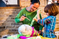 Mother and son decorating pinata at home