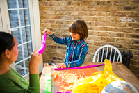 Mother and son playing with pinata at home