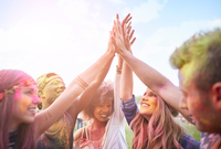 Group of friends at festival, covered in colourful powder paint, joining hands 11015298585| 写真素材・ストックフォト・画像・イラスト素材|アマナイメージズ